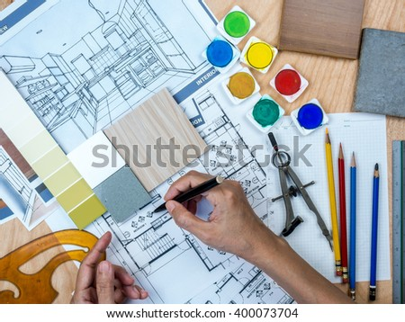 Top view of architect & interior designer working at worktable with blue print, freehand sketch / Real estate business conceptual