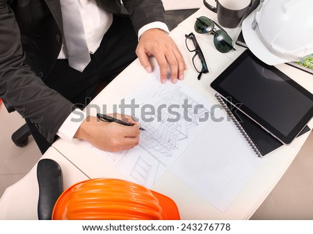 top view of architect working table with drawing perspective building plan and sunglasses ,safety helmet - stock photo