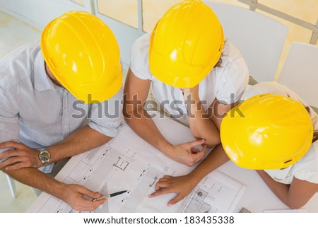 Top view of architects in yellow helmets working on blueprints at the office - stock photo