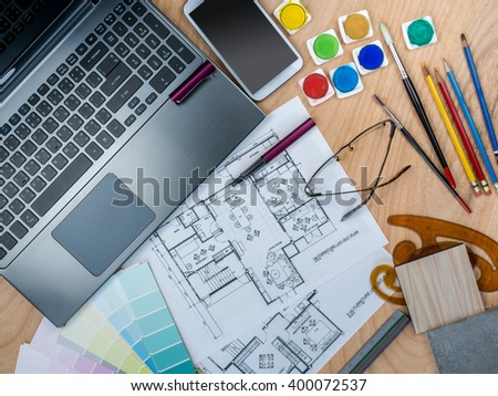 Top view of artistic worktable with laptop & blue print/ Real estate business conceptual