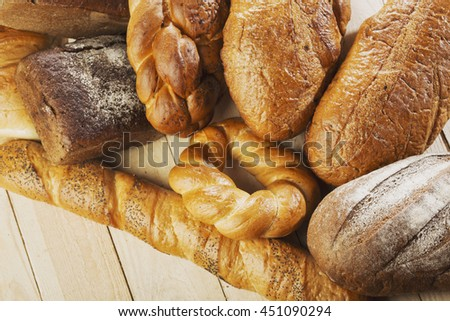 Top view of assortment of different kind of cereal bakery: bread, pasties, buns, on wooden background. - stock photo