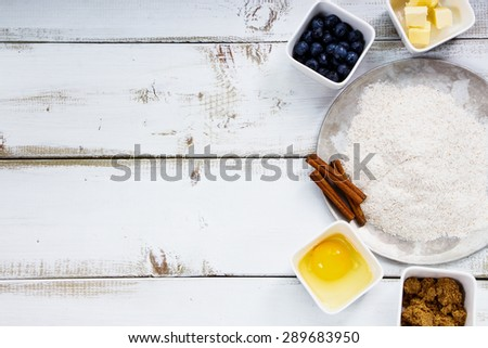 Top view of baking ingredients eggs, flour, sugar, butter, berries over white wooden background. Dough preparation. - stock photo