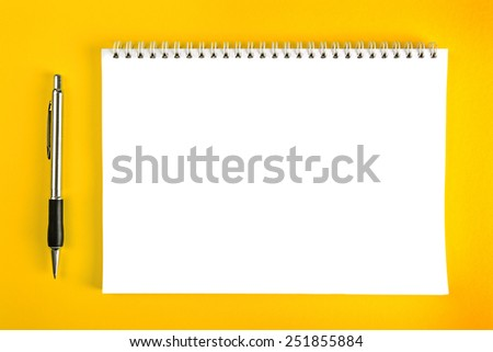 Top View of Ballpoint Pen and Blank Paper Notebook with Spiral Binding as Business Copy Space on Yellow Background. - stock photo