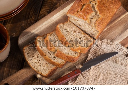Top view of banana nut bread sliced on a wooden cutting board