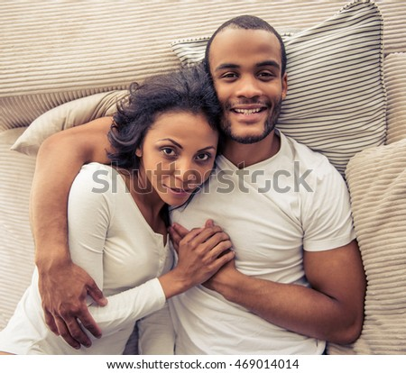 Top view of beautiful young Afro American couple hugging, looking at camera and smiling, lying on sofa at home