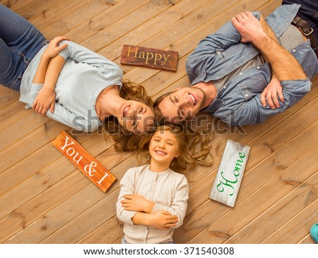 Top view of beautiful young family looking in camera and smiling while lying on wooden floor at home. Three wooden plates lying near the family. - stock photo