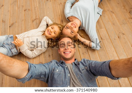 Top view of beautiful young family looking in camera and smiling while lying on wooden floor at home. Father making selfie. - stock photo
