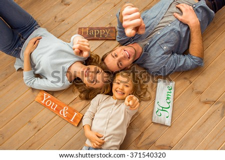 Top view of beautiful young family looking in camera, smiling and pointing in camera while lying on wooden floor at home - stock photo