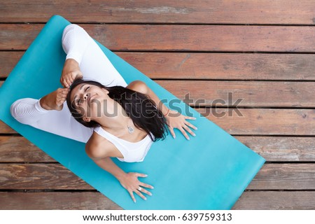 Top View Of Beautiful Young Fitness Woman Working Out On Wooden Floore Terrace Doing Yoga