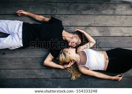 Top view of beautiful young loving couple lying together on the hardwood floor and looking at each other
