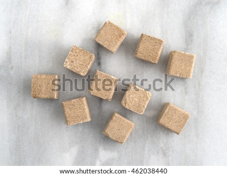 Top view of beef flavored bouillon cubes gray marble cutting board.