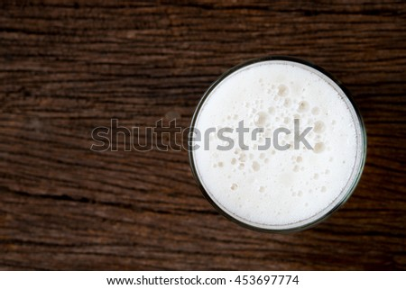 top view of beer glass with foam on old wood table