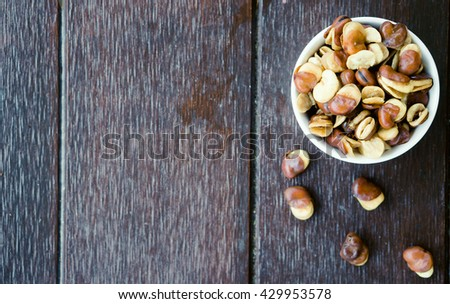 Top view of belted broad bean in the white bowl on wooden background.Nuts Concept.Broad bean. - stock photo