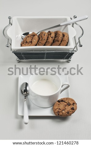 Top view of biscuits in white ceramic plate, spoons  and cup of milk on white wooden background - stock photo