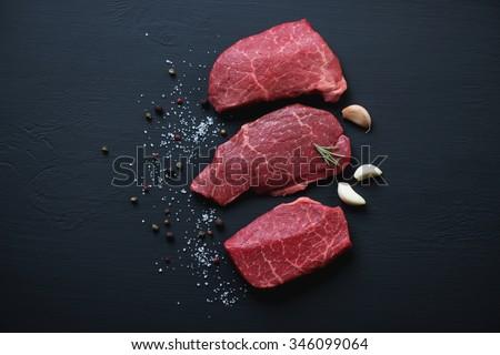 Top view of black angus beef steaks with seasonings, studio shot - stock photo