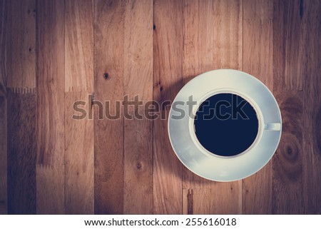 Top view of black coffee in the cup on wooden table  - soft focus with vintage color effect - stock photo