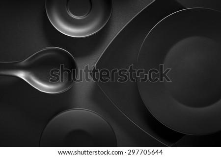 Top view of black empty plates on dark grey background. - stock photo
