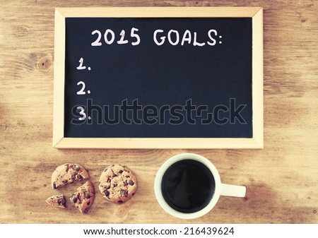 top view of blackboard with the phrase 2015 goals over wooden board with coffee and cookies - stock photo