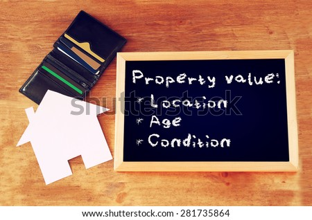top view of blackboard with the phrase property value, open wallet and paper house shape - stock photo