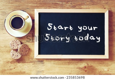 top view of blackboard with the phrase start your story today next to cup of black coffee and cookies - stock photo