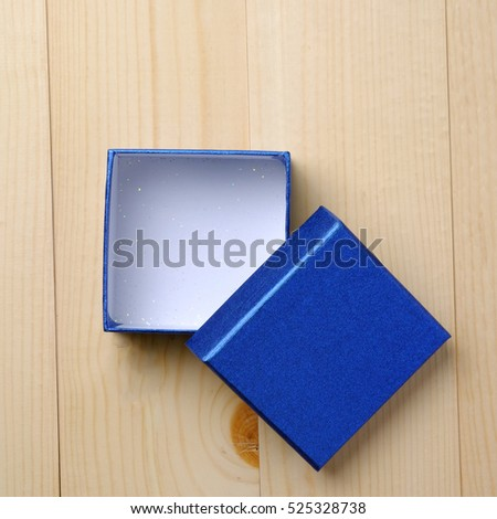 Top view of blank blue box for important day on wood table, decorated and vintage style.