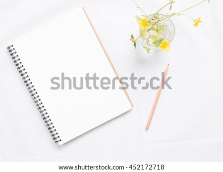 Top view of blank notebook and flower on white workspace background. - stock photo