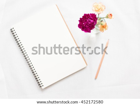 Top view of blank notebook and flower on white workspace background. Focus flowers. - stock photo