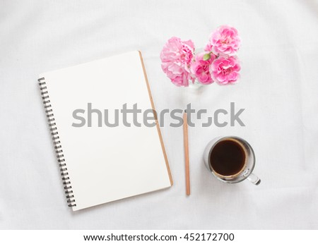 Top view of blank notebook and flower on white workspace background. Focus notebook. - stock photo