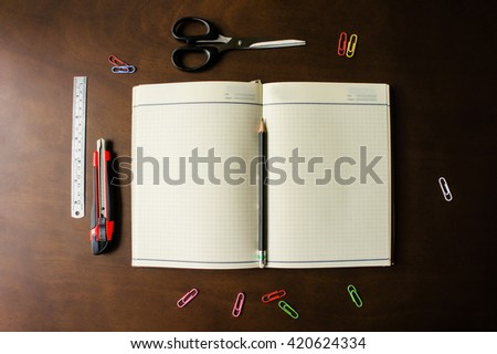 Top view of blank notebook and school supplies on the dark wood background - stock photo