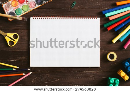 Top view of blank notebook and school supplies on the dark wood background, Retro toned photo. - stock photo