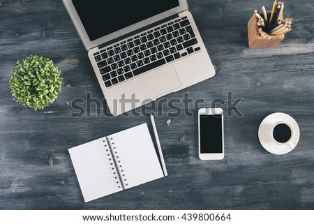 Top view of blank spiral notepad, smartphone, coffee cup, laptop, plant and other items on dark wooden office desktop. Mock up - stock photo
