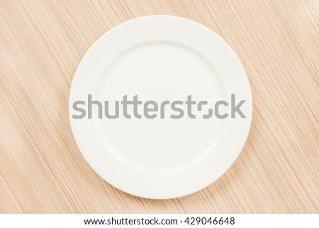 Top view of blank white dish on a wood background. - stock photo