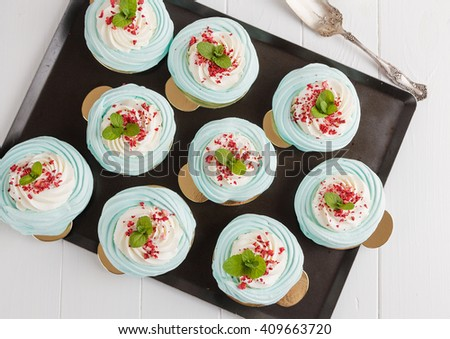 Top view of blue mini pavlova meringue cakes with cream cheese on white background. Shallow focus - stock photo