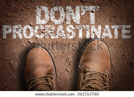 Top View of Boot on the trail with the text: Don't Procrastinate - stock photo