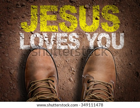 Top View of Boot on the trail with the text: Jesus Loves You - stock photo