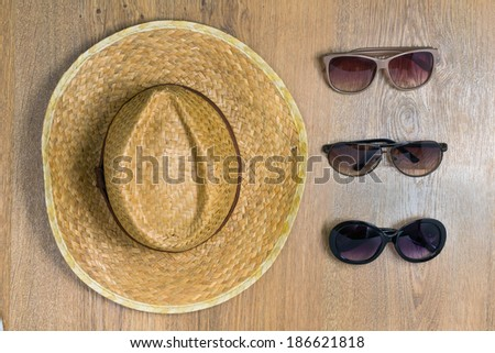 Top view of braided hat and three pair of glasses on a wooden background. Travel concept - stock photo