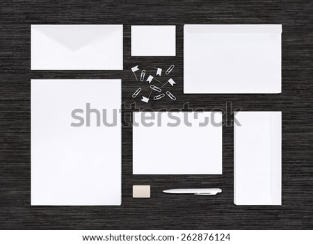 Top view of branding identity mockup with different paper templates for design presentation or portfolio on black table. Includes envelopes, sheets, business card, pen, eraser, clips. - stock photo