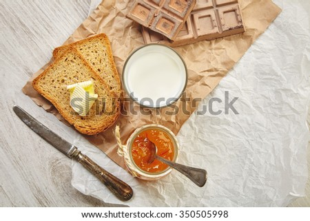 Top view of breakfast set with chocolate, jam, dry toast bread, butter and milk. Everything on craft paper and  vintage knife and spoon with patina. - stock photo
