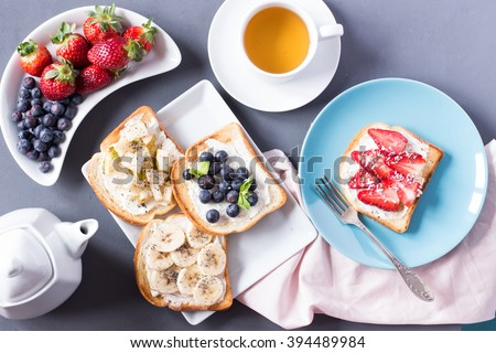 Top view of breakfast table with toast, tea, berries - stock photo
