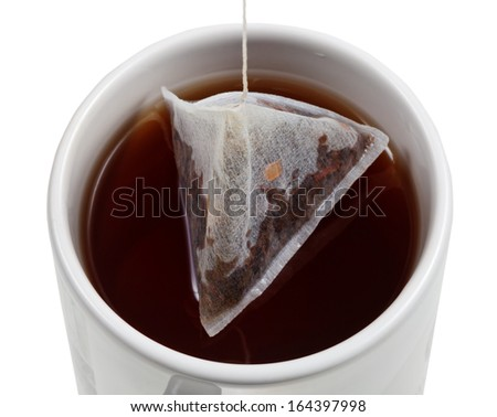 top view of brewing of tea in mug with tea bag close up isolated on white background - stock photo