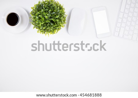 Top view of bright office desktop with blank white mobile phone, computer mouse, keyboard, coffee cup and decorative plant. Mock up - stock photo
