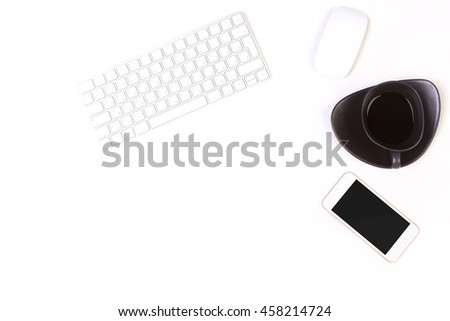 Top view of bright white office desktop with computer mouse, keyboard, coffee cup and blank smartphone. Mock up - stock photo