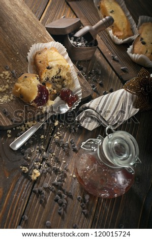 Top view of broken cupcake, iron spoon, jar with jam and scattered chocolate drops make in the dark tonality. - stock photo