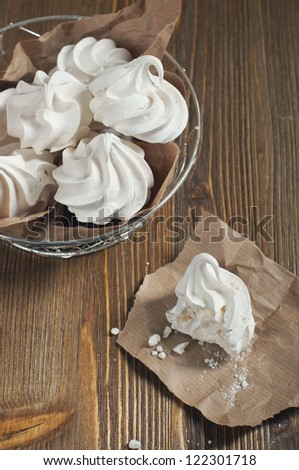 Top view of broken meringue with crumbs on paper and lot of meringues in iron bowl on dark wooden background - stock photo