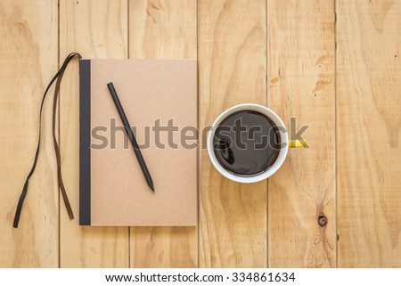Top view of brown book and coffee cup on wooden table background - stock photo