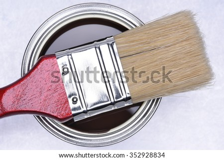Top view of brown paint can with red brush on grey metal background - stock photo
