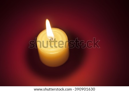 Top view of burning candle on red background. - stock photo