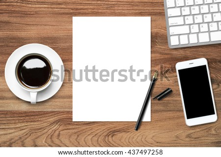 Top view of business desk table with blank paper and pen in the middle, coffee and IT supplies. Top view, flat lay. - stock photo
