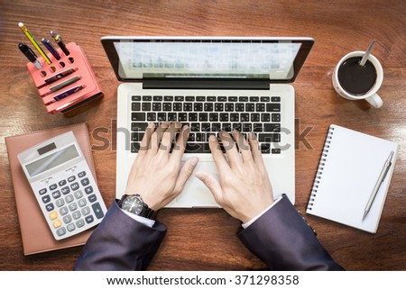 Top view of business man hands working on laptop or tablet pc on wooden desk. - stock photo