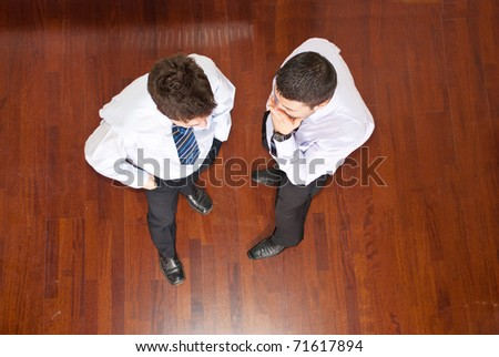Top view of business man telling his collegue a secret and holding hands to month and the other man listening him